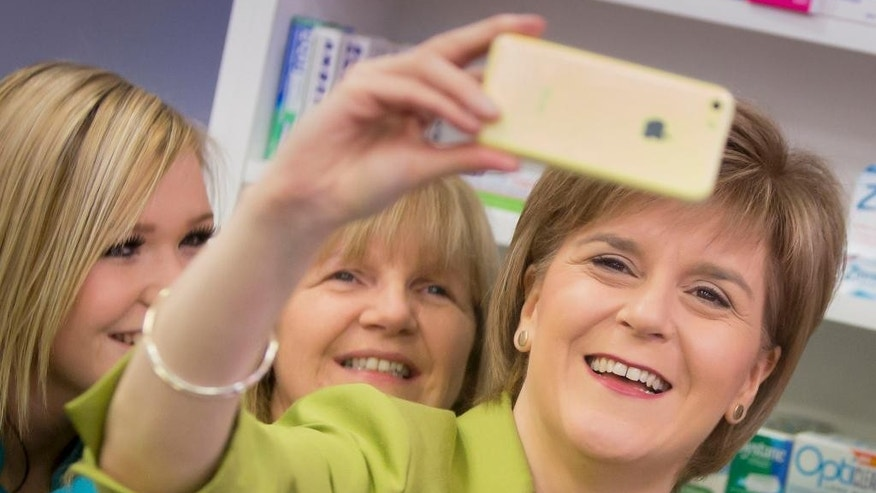 In this April 3, 2015 photo, Scotland's First Minister Nicola Sturgeon takes a selfie with staff during a visit to Corstorphine Pharmacy in Edinburgh, Scotland. Sturgeon, the Scottish National Party leader, was in Edinburgh on the election campaign trail. Britain's Labour Party leader Ed Miliband's crusade to bring the Labour Party back to power after five years in opposition has struck a roadblock in Scotland, where the party is experiencing a dramatic drop in what had long been a reliable stronghold.  In the aftermath of a spirited referendum on independence last fall, Scotland is moving away from its traditional Labour Party voting habits in favor of the Scottish National Party, which favors splitting off from the rest of Britain.  (AP Photo/PA, Danny Lawson)  UNITED KINGDOM OUT; NO SALES; NO ARCHIVES