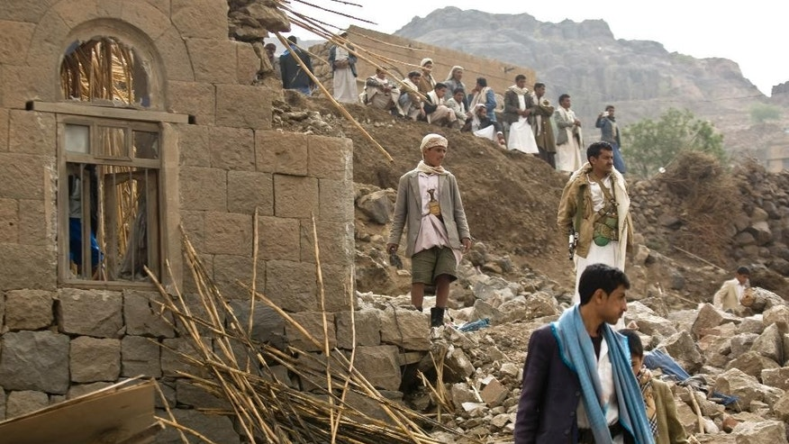 FILE - In this Saturday, April 4, 2015 file photo, Yemenis stand amid the rubble of houses destroyed by Saudi-led airstrikes in a village near Sanaa, Yemen. Since their advance began last year, the Shiite rebels, known as Houthis have overrun Yemen's capital, Sanaa, and several provinces, forcing the country's beleaguered President Abed Rabbo Mansour Hadi to flee the country. A Saudi-led coalition continued to carry out intensive airstrikes overnight and early Saturday morning targeting Houthi positions. (AP Photo/Hani Mohammed, File)