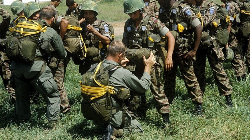 U.S. Army soldiers check the equipment of Colombian paratroopers. (Photo: Department of Defense)