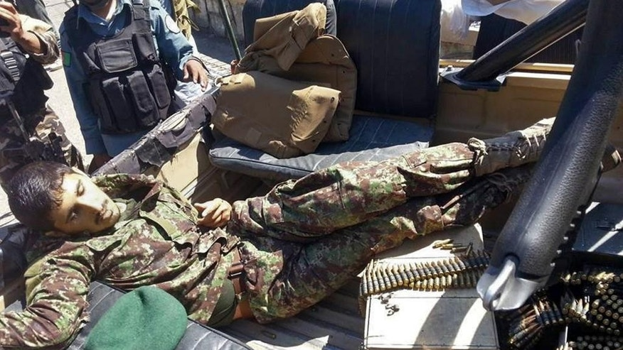 The body of an Afghan national army soldier lies in an army vehicle after he opened fire on U.S. troops, in the compound of the provincial governor, Jalalabad, east of Kabul, Afghanistan, Wednesday, April 8, 2015. The Afghan soldier opened fire on U.S. troops in Afghanistan on Wednesday, wounding three before he was shot dead by American troops, an official and an eyewitness said. The incident happened after a meeting between Afghan provincial leaders and a U.S. Embassy official. (AP Photo)