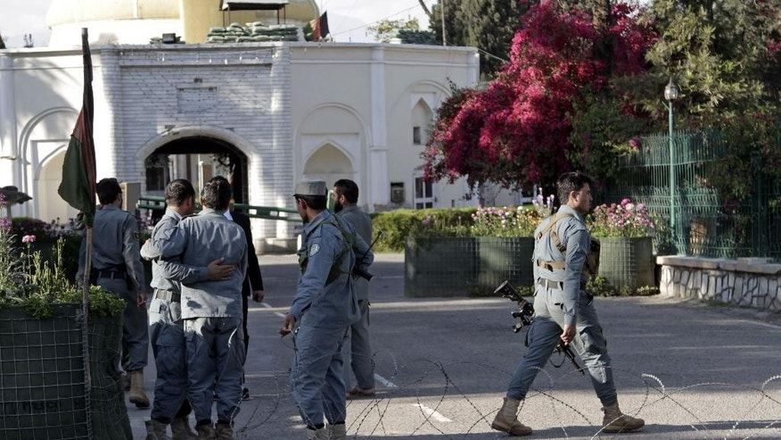 Afghan policemen console each other at the site of a deadly attack by an Afghan national army soldier who opened fire on U.S. troops, in the compound of the provincial governor, Jalalabad, Afghanistan, Wednesday, April 8, 2015. A U.S. official said an American soldier was killed in the shooting incident in the eastern Afghan city of Jalalabad in which at least two other U.S. troops were wounded when an Afghan soldier opened fire at them. The incident happened after a meeting Wednesday between Afghan provincial leaders and a U.S. Embassy official in the compound of the provincial governor in Jalalabad. (AP Photo/Rahmat Gul)