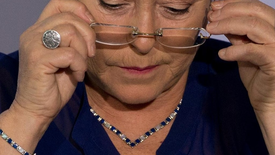 FILE - In this Dec. 9, 2014 file photo, Chile's President Michelle Bachelet puts on her glasses during a 2014 Iberoamerican Summit event in Veracruz, Mexico. Bachelet's approval rating is at her lowest level ever, but she said Wednesday, April 8, 2015, that she doesn't care about her popularity, as she's focused on the well-being of Chile and pushing forward needed reforms. (AP Photo/Rebecca Blackwell, File)