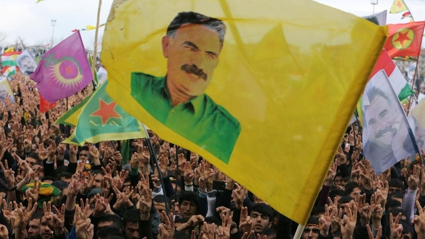 FILE - In this Saturday, March 21, 2015 file photo, supporters hold flags showing the image of imprisoned Kurdish rebel leader Abdullah Ocalan during the Nowruz celebrations in southeastern Turkish city of Diyarbakir, Turkey. The peace process to end decades of violent strife between Turkey and Kurdish rebels has been one of Turkish leader Recep Tayyip Erdogan's signature achievements. But with key parliamentary elections looming in June, the president has hit the brakes on peace talks _ and exposed a rare rift within his own party. (AP Photo/Burhan Ozbilici, File)