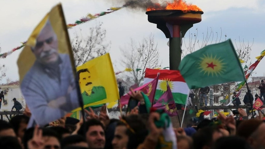With a traditional Nowruz fire in the background, supporters hold posters of imprisoned Kurdish rebel leader Abdullah Ocalan during the Nowruz celebrations in southeastern Turkish city of Diyarbakir, Turkey, Saturday, March 21, 2015. The peace process to end decades of violent strife between Turkey and Kurdish rebels has been one of Turkish leader Recep Tayyip Erdogan's signature achievements. But with key parliamentary elections looming in June, the president has hit the brakes on peace talks _ and exposed a rare rift within his own party. (AP Photo/Burhan Ozbilici, File)