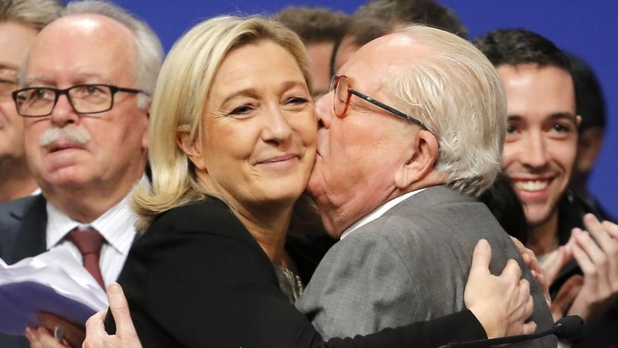 """FILE - In this Sunday Nov. 30, 2014 file photo, French far-right Front National leader Marine Le Pen is kissed by her father Jean-Marie Le Pen after being re-elected as president of the party during the 15th congress of the party, in Lyon, central France. Marine Le Pen has launched an all-out offensive against her father, party founder Jean-Marie Le Pen, saying on Wednesday April 8, 2015, she will oppose his candidacy in upcoming elections and condemning as """"political suicide"""" his repeated comments that the Nazi gas chambers were a """"detail in history.""""  (AP Photo/Laurent Cipriani, File)"""