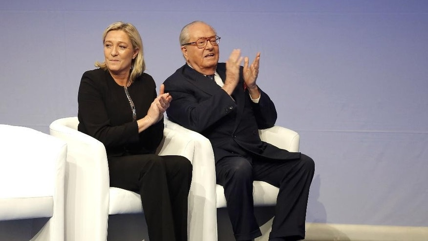 """FILE - In this Saturday Nov. 29, 2014 file photo, French far-right Front National leader Marine Le Pen and her father Jean-Marie Le Pen applaud during the 15th congress of the party, in Lyon, central France. Marine Le Pen has launched an all-out offensive against her father, party founder Jean-Marie Le Pen, saying she will oppose his candidacy in upcoming elections and condemning as """"political suicide"""" his repeated comments that the Nazi gas chambers were a """"detail in history."""" (AP Photo/Laurent Cipriani, File)"""