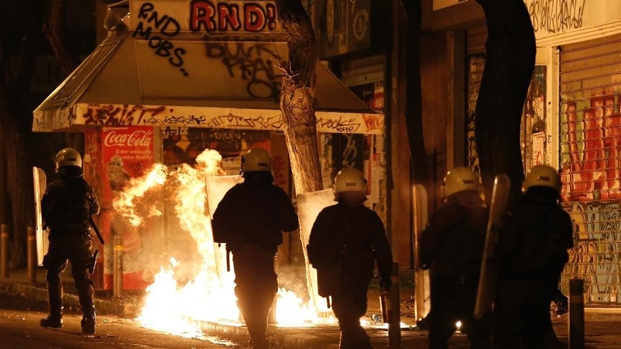Greek riot police walk next a patrol bomb thrown by rioting youths during clashes after a demonstration by about 700 anarchists seeking the abolition of a maximum security prison, in central Athens, on Tuesday, April 7, 2015. Dozens of rioters burnt at least two cars, smashed a shopfront and threw petrol bombs and stones at police, who responded with tear gas. Four suspected rioters were detained, while no injuries were reported. (AP Photo/Petros Giannakouris)