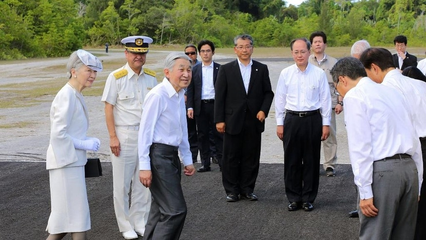 Emperor Akihito, third left, and Empress Michiko, left, arrive on Pelelilu island in Palau Thursday, April 9, 2015. The emperor of Japan is visiting a remote Pacific island to pray for thousands of Japanese and American soldiers who died during the World War II battle of Pelelilu.(AP Photo/Kyodo News) JAPAN OUT, MANDATORY CREDIT