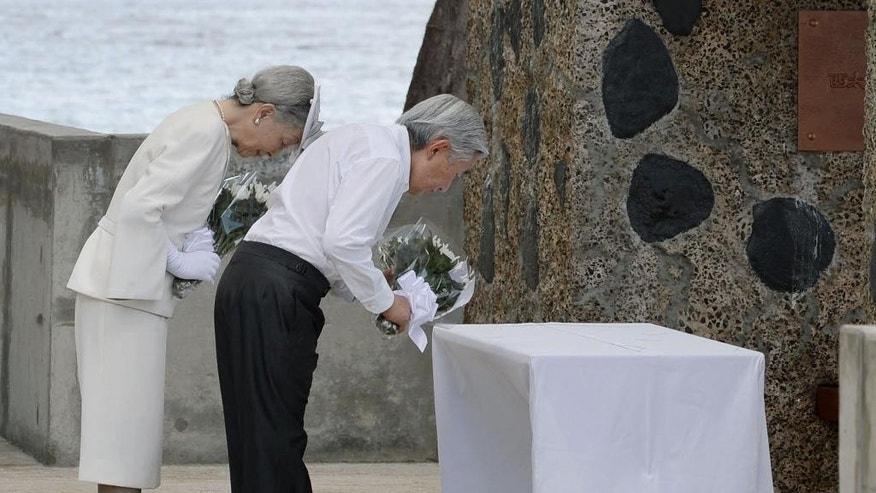 Emperor Akihito and Empress Michiko offer flowers in front of the cenotaph on Pelelilu island in Palau Thursday, April 9, 2015. The emperor of Japan is visiting a remote Pacific island to pray for thousands of Japanese and American soldiers who died during the World War II battle of Pelelilu.(AP Photo/Kyodo News) JAPAN OUT, MANDATORY CREDIT