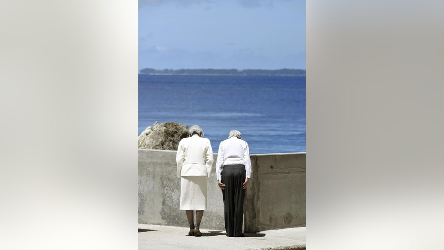 Japan's Emperor Akihito and Empress Michiko bow toward Angaur island, seen in the background, after they offered flowers at the cenotaph on Pelelilu island in Palau Thursday, April 9, 2015. The emperor of Japan is visiting a remote Pacific island to pray for thousands of Japanese and American soldiers who died during the World War II battle of Pelelilu.(AP Photo/Kyodo News) JAPAN OUT, MANDATORY CREDIT