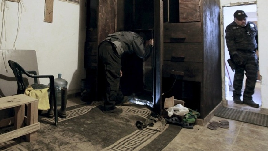 April 7, 2015: A policeman checks the access to a suspected drug tunnel under construction, which is located inside a wardrobe, during a media tour by Mexican Army in Tijuana.