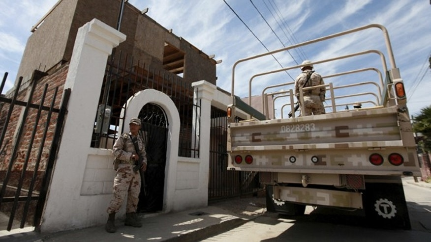 April 7, 2015: Soldiers stand guard outside a house, where a suspected drug tunnel under construction was located, during a media tour by Mexican Army in Tijuana.