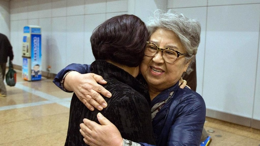 "Sandra Suh, right, hugs an unidentified woman at the arrival gate of the Beijing Capital International Airport in Beijing, Thursday, April 9, 2015. North Korea has deported the American woman who frequently visited the country over the past 20 years, accusing her of engaging in ""plot-breeding and propaganda.""(AP Photo/Ng Han Guan)"