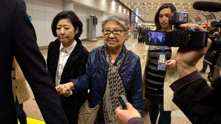 "Sandra Suh, center, holds the hand of an unidentified woman as they walk from the arrival gate of Beijing Capital International Airport in Beijing, Thursday, April 9, 2015. North Korea has deported the American woman who frequently visited the country over the past 20 years, accusing her of engaging in ""plot-breeding and propaganda.""(AP Photo/Ng Han Guan)"