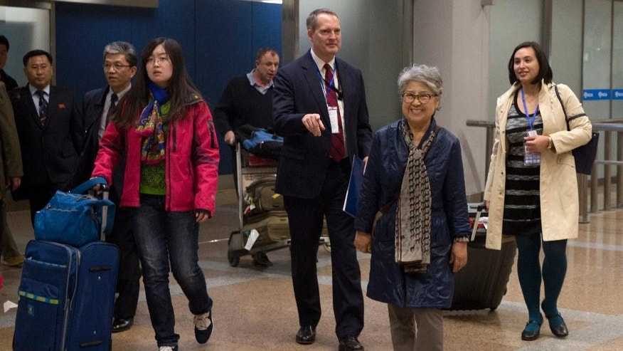 "Sandra Suh, second from right, walks out from the arrival gate of Beijing Capital International Airport in Beijing, Thursday, April 9, 2015. North Korea has deported the American woman who frequently visited the country over the past 20 years, accusing her of engaging in ""plot-breeding and propaganda.""(AP Photo/Ng Han Guan)"