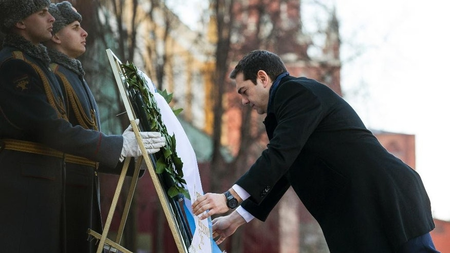 Greek Prime Minister Alexis Tsipras adjusts a ribbon as he takes part in a wreath laying ceremony at the Tomb of the Unkown Soldier in Moscow, Russia, Wednesday, April 8, 2015. Tsipras is on an official visit to Russia. (AP Photo/Ivan Sekretarev, Pool)