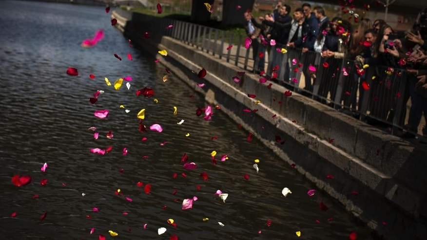 Members of Spain's gypsy community throw flower petals into the Manzanares river, symbolizing the departure of their ancestors from India and their exodus across the world during an event in memory of the Roma victims of the Nazi Holocaust in Madrid, Spain, Wednesday, April. 8, 2015. Spanish groups representing gypsies have launched a campaign to remove a reference to them as swindlers from the world's benchmark Spanish dictionary. Foundation spokeswoman Pilar Calon says the effort attempts to raise awareness of discrimination against gypsies, also known as Roma. Spain has about 750,000 people of Roma heritage. (AP Photo/Andres Kudacki)