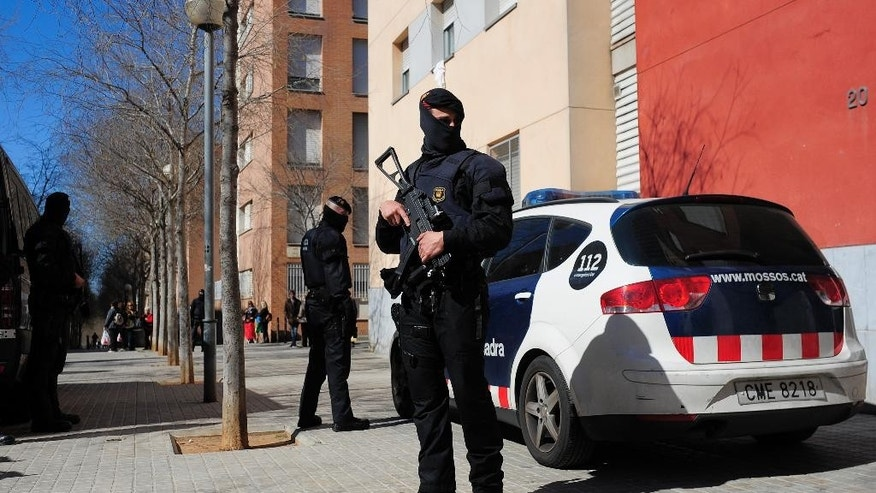 Mossos d'Esquadra regional police officers stand guard during a raid in one of the region's biggest operations against jihad activity in Sabadell, near Barcelona, Spain, Wednesday, April 8, 2015. Police in northeastern Spain say they have arrested 10 people for suspected links to jihad terror activity and the Islamic State armed group. A Catalan regional police statement said the arrests took place Wednesday in five northeastern towns, including the regional capital of Catalonia, Barcelona. (AP Photo/Manu Fernandez)
