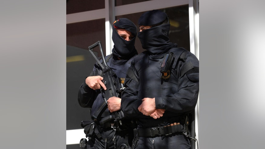 Mossos d'Esquadra regional police officers stand guard during a raid in one of the region's biggest operations against jihadi activity in Sabadell, near Barcelona, Spain, Wednesday, April 8, 2015. Police in northeastern Spain say they have arrested 10 people for suspected links to jihadi terror activity and the Islamic State armed group. A Catalan regional police statement said the arrests took place Wednesday in five northeastern towns, including the regional capital of Catalonia, Barcelona. (AP Photo/Manu Fernandez)