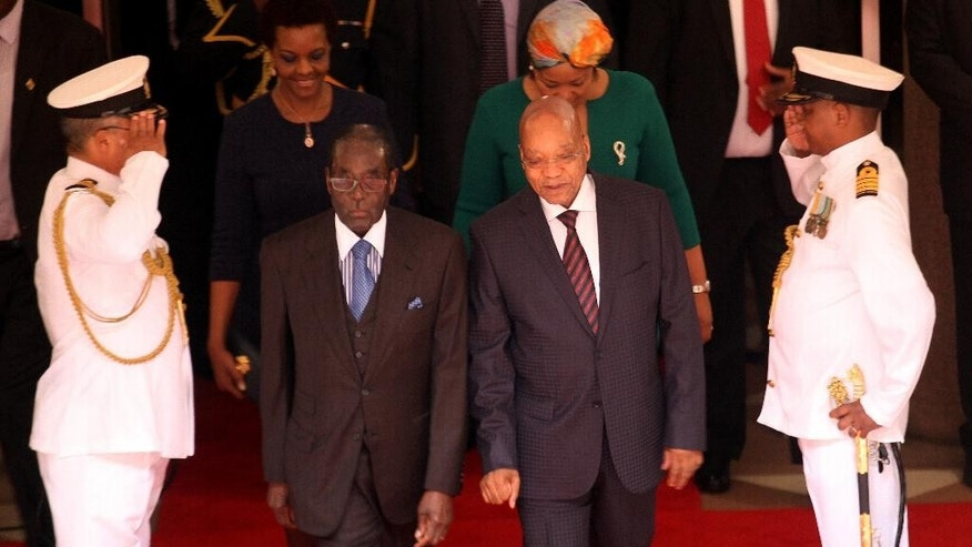 Zimbabwean President, Robert Mugabe, second from and left, and his South African counterpart, Jacob Zuma, second from right, arrive for a welcoming ceremony at the government's Union Building in Pretoria, South Africa, Wednesday, April 8, 2015. Mugabe is on a two-day state visit to the country. (AP Photo/Denis Farrell)