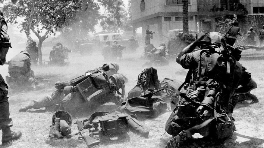 FILE - In this April 13, 1975, file photo, U.S. Marines come under Khmer Rouge fire while they were on the ground near the U.S. embassy during Operation Eagle Pull which evacuated American and embassy personnel in Phnom Penh, Cambodia. Five days after Operation Eagle Pull, the dramatic evacuation of Americans, the U.S.-backed government fell as communist Khmer Rouge guerrillas stormed into Phnom Penh. Nearly 2 million Cambodians - one in every four - would die from executions, starvation and hideous torture. (AP Photo/Tea Kim Heang, File)