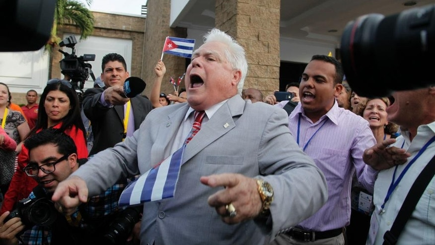 A man shouts slogans against pro-government supporters from Cuba and Venezuela outside the Vasco Nunes De Balboa Convention Center in Panama City, Wednesday, April 8, 2015. About 100 supporters of Cuba's government aggressively heckled dissidents from the communist-run island attending a civil society forum Wednesday at the start of the Summit of the Americas in Panama. (AP Photo/Ismael Francisco, Cubadebate)