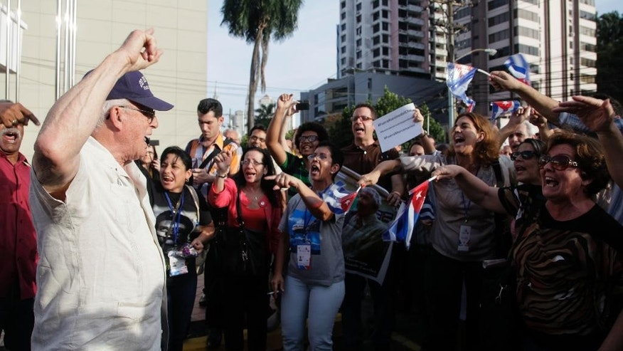 A man shouts slogans against Cuban pro-government supporters outside the Vasco Nunes De Balboa Convention Center in Panama City, Wednesday, April 8, 2015. About 100 supporters of Cuba's government aggressively heckled dissidents from the communist-run island attending a civil society forum Wednesday at the start of the Summit of the Americas in Panama. (AP Photo/Cubadebate, Ismael Francisco)