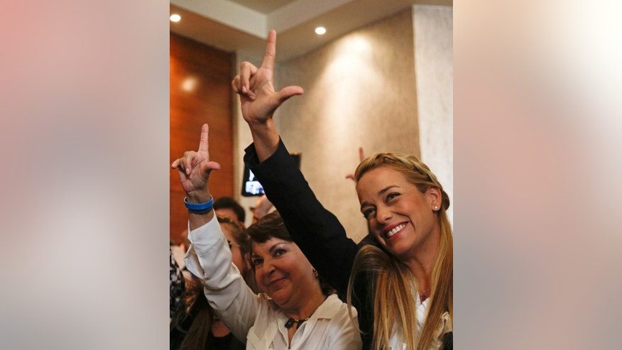 "Venezuelan Lilian Tintori, wife of jailed opposition leader Leopoldo Lopez, right, and Venezuelan Mitzy Capriles de Ledezma, wife of imprisoned Caracas Mayor Antonio Ledezma gesture an ""L"" for ""libre,"" or ""free"" during a press conference in Panama City, Thursday, April 9, 2015. In a document presented at the press conference, about two dozen former leaders of Spain and Latin America critical of the government of Venezuelan President Nicolas Maduro called on the region to put aside ""complacent silence"" and demand that Venezuela's upcoming parliamentary elections be conducted without political prisoners and with observers, as a possible solution to the South American nation's political crisis. (AP Photo/Arnulfo Franco)"