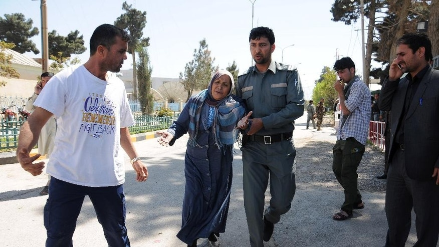 A member of Afghan security forces helps woman when gunmen stormed a government compound in Mazar-e-sharif, north of Kabul, Afghanistan, Thursday, April, 9, 2015. An Afghan official says the attack in the northern city killed a policeman and wounded several people. (AP Photo/Mustafa Najafizada)