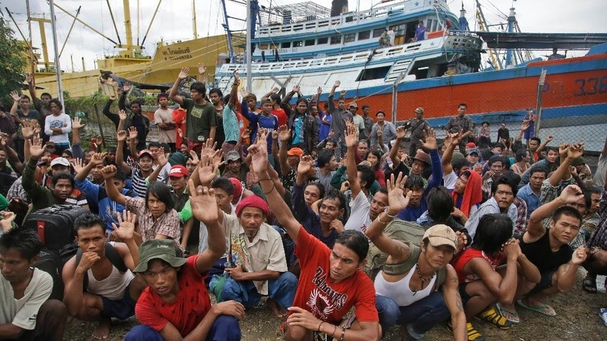 FILE - In this Friday, April 3, 2015 file photo, Burmese fishermen raise their hands as they are asked who among them want to go home at the compound of Pusaka Benjina Resources fishing company in Benjina, Aru Islands, Indonesia. Hundreds of foreign fishermen on Friday rushed at the chance to be rescued from the isolated island where an Associated Press report revealed slavery runs rampant in the industry.  The number of enslaved fisherman found on the remote Indonesian island has now reached nearly 550, after a fact-finding team returned on Thursday, April 9, to make sure no one had been left behind. (AP Photo/Dita Alangkara, File)