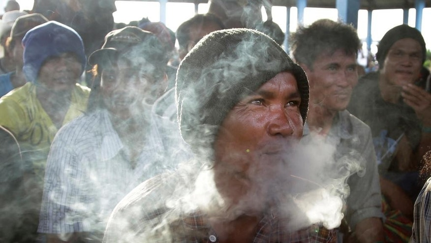 In this April 4, 2015 file photo, a rescued Cambodian fisherman blows cigarette smoke while waiting to be registered upon arrival in Tual, Indonesia. He was one of hundreds of migrant workers revealed in an Associated Press investigation to have been lured or tricked into leaving their countries and were brought to Indonesia to be forced to catch seafood.  The number of enslaved fisherman found on a remote Indonesian island has now reached nearly 550, after a fact-finding team returned on Thursday, April 9, to make sure no one  had been left behind in the dramatic rescue nearly a week ago of 330 migrants from Benjina.(AP Photo/Dita Alangkara, File)