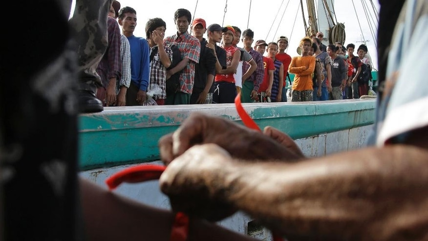 FILE - In this Saturday, April 4, 2015 file photo, an Indonesian official put on wrist bands on recently rescued Burmese fishermen for identification purpose upon their arrival in Tual, Indonesia.  The Burmese men were among hundreds of migrant workers revealed in an Associated Press investigation to have been lured or tricked into leaving their countries and were brought to Indonesia to be forced to catch seafood.  The number of enslaved fisherman found on a remote Indonesian island has now reached nearly 550, after a fact-finding team returned on Thursday, April 9, to make sure no one  had been left behind in the dramatic rescue nearly a week ago of 330 migrants from Benjina.(AP Photo/Dita Alangkara, File)