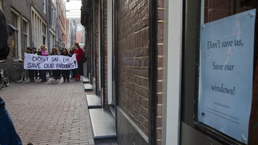 Prostitutes and sympathizers take to the streets in Amsterdam, Netherlands, Thursday, April 9, 2015, to protest plans to clean up the city's famed red light district by shuttering windows where scantily-clad sex workers pose to attract potential clients.  Prostitutes say that the closures are depriving them of safe places to work. (AP Photo/Peter Dejong)