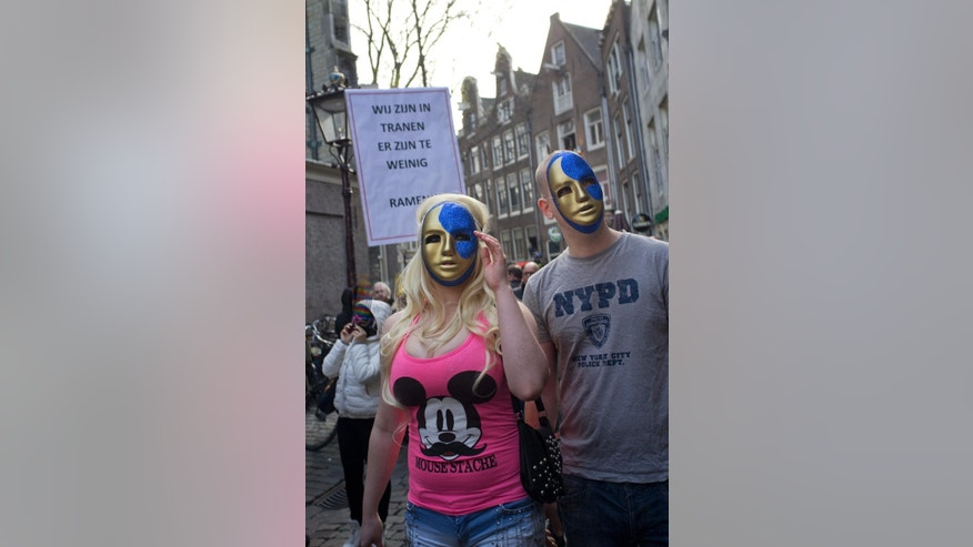 "A banner reads ""We Are in Tears, There's To Few Windows"" as a group of masked prostitutes and sympathizers take to the streets in Amsterdam, Netherlands, Thursday, April 9, 2015, to protest plans to clean up the city's famed red light district by shuttering windows where scantily-clad sex workers pose to attract clients. Prostitutes say that the closures are depriving them of safe places to work. (AP Photo/Peter Dejong)"