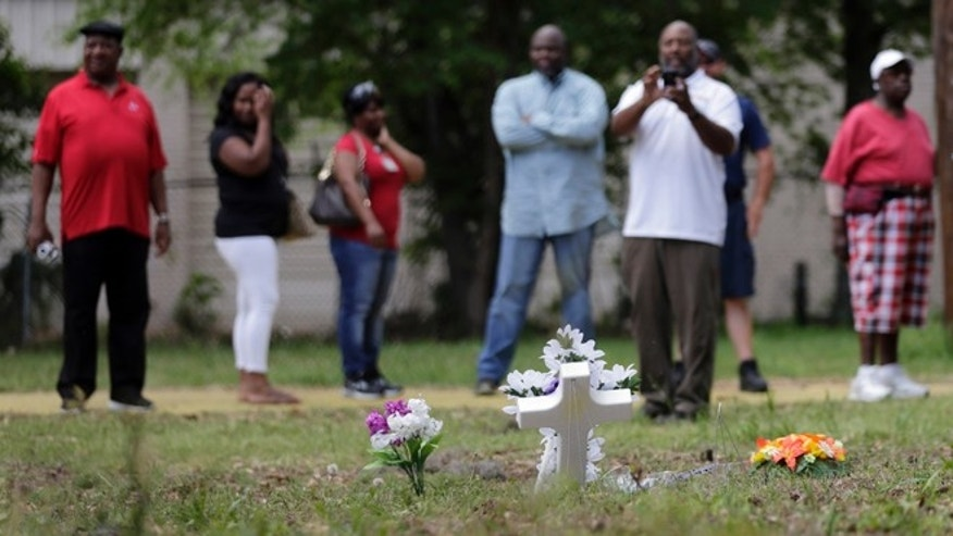 A man takes a photo as others look at a memorial and flowers placed near the site where Walter Scott was killed in North Charleston, S.C., Wednesday, April 8, 2015. Scott was killed by a North Charleston police officer after a traffic stop on Saturday. The officer has been charged with murder. (AP Photo/Chuck Burton)