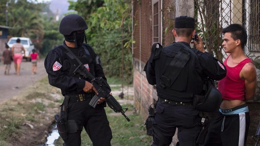 In this April 1, 2015 photo, a man is detained by police special forces in the town of San Juan Opico, El Salvador. The man was detained in what police called a known gang area for not having identification and for having, what police said, the phone numbers of other gang members in his cell phone. Authorities say a recent violent spike is the result of gangs trying to pressure the government to negotiate issues raised as part of a 2-year truce that fell apart in 2014. Others see it as a reaction to the new government's iron-fist approach to the country's two major gangs, Mara Salvatrucha and 18th Street. (AP Photo/Salvador Melendez)