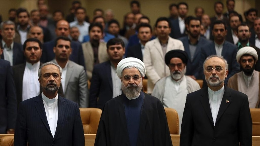 Iranian President Hassan Rouhani, center, accompanied by the head of Iran's Atomic Energy Organization Ali Akbar Salehi, right, and his chief of staff Mohammad Nahavandian, listens to Iran's national anthem while attending a ceremony marking National Nuclear Technology Day, in Tehran, Iran, Thursday, April 9, 2015. Rouhani warned that Tehran will not sign on to a final nuclear deal with world powers unless it is predicated on the lifting of economic sanctions imposed on Iran over the controversial nuclear program. (AP Photo/Vahid Salemi)