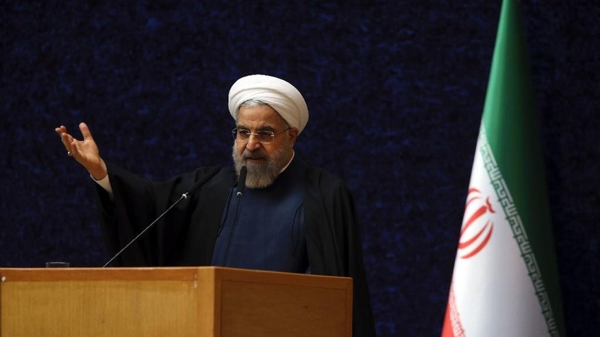 Iranian President Hassan Rouhani delivers his speech in a ceremony marking National Nuclear Technology Day, in Tehran, Iran, Thursday, April 9, 2015. Rouhani warned that Tehran will not sign on to a final nuclear deal with world powers unless it is predicated on the lifting of economic sanctions imposed on Iran over the controversial nuclear program. (AP Photo/Vahid Salemi)