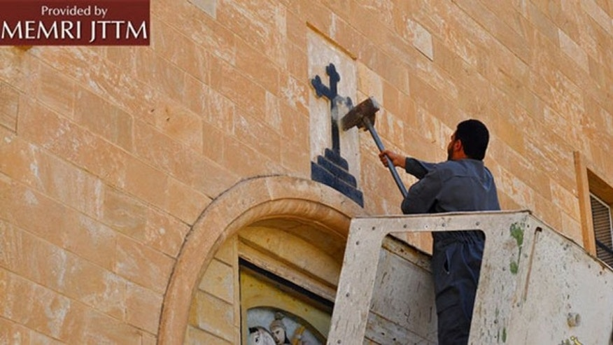 ISIS men destroy various Christian symbols in Nineveh, Iraq.
