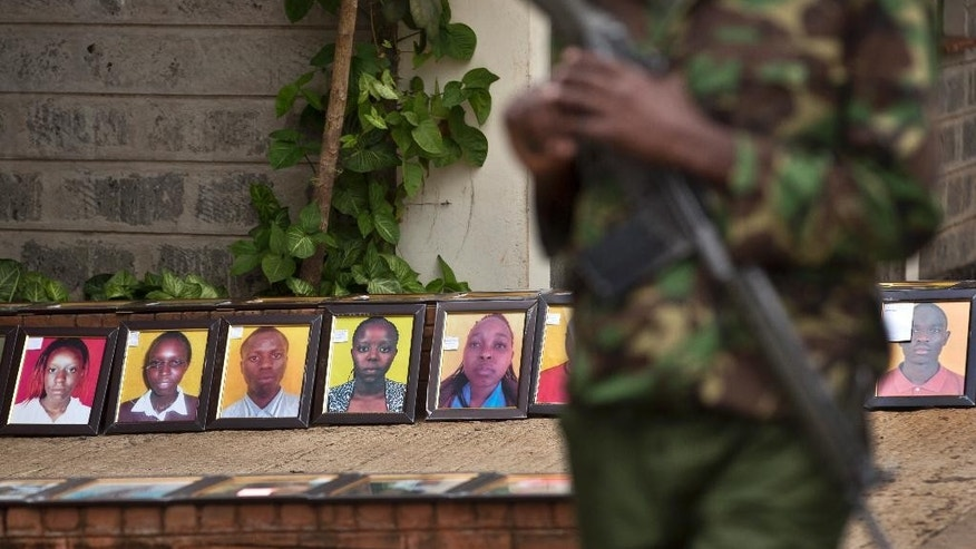A member of Kenya's security forces walks past a row of photographs of some of those killed in the Garissa attack, which families were asked to bring to accompany the bodies after they are released for burial, at the Chiromo Funeral Parlour in Nairobi, Kenya Thursday, April 9, 2015. A week after the attack by extremist group al-Shabab on Garissa University College, relatives of the deceased continued their wait Thursday for the bodies to be released, hoping to be able to arrange their burials. (AP Photo/Ben Curtis)