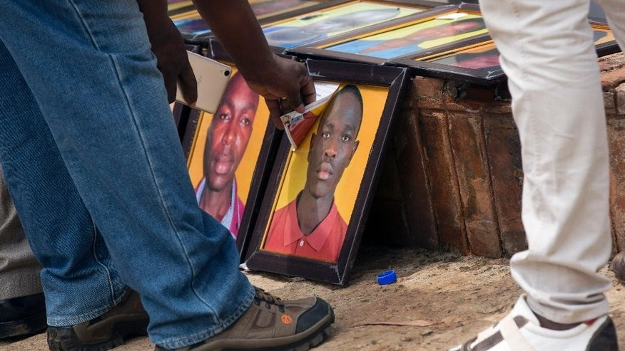 A man looks at one in a row of photographs of some of those killed in the Garissa attack, which families were asked to bring to accompany the bodies after they are released for burial, at the Chiromo Funeral Parlour in Nairobi, Kenya Thursday, April 9, 2015. A week after the attack by extremist group al-Shabab on Garissa University College, relatives of the deceased continued their wait Thursday for the bodies to be released, hoping to be able to arrange their burials. (AP Photo/Ben Curtis)