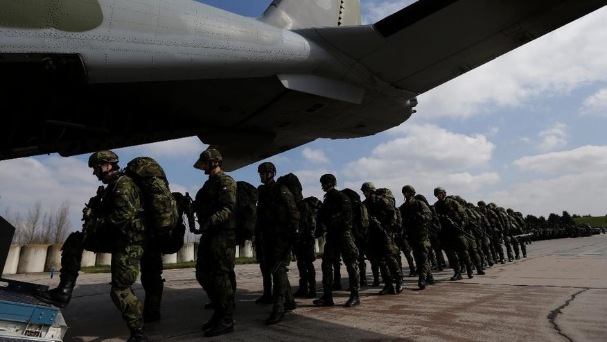 "Czech Republic's soldiers from the 43rd airborne battalion line up to board an aircraft during the NATO drill ""The Noble Jump"" at the airport in Pardubice, Czech Republic, Thursday, April 9, 2015. NATO is completing an initial exercise and first testing of its new rapid response force that has been created to face new challenges from Russia. (AP Photo/Petr David Josek)"