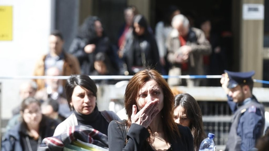 A woman cries as she is evacuated from the tribunal building in Milan, Italy, after a shooting was reported inside a courtroom Thursday, April 9, 2015. Italy's interior minister says the gunman who opened fire in Milan's courthouse has been detained as he tried to flee.  At least one judge was shot and killed Thursday morning by the gunman, who was in the courthouse for a bankruptcy proceeding. (AP Photo/Luca Bruno)