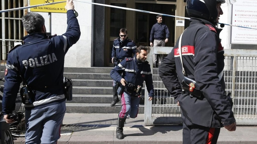 Policemen run out of the tribunal building in Milan, Italy, after a shooting was reported inside a courtroom Thursday, April 9, 2015. (AP Photo/Luca Bruno)