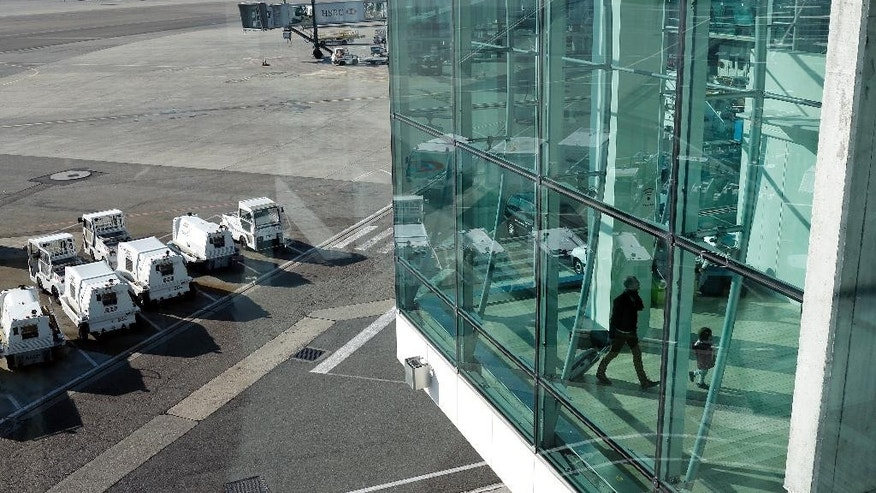 Travelers walk in the Lyon Airport, central France, Thursday, April 9, 2015. French air traffic controllers called a two-day strike in a quarrel over working and retirement conditions, prompting the cancellation of 50 percent of flights across France. (AP Photo/Laurent Cipriani)
