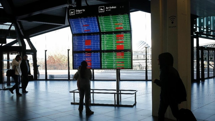 A traveler looks at a departure board at Lyon Airport, central France, Thursday, April 9, 2015. French air traffic controllers called a two-day strike in a quarrel over working and retirement conditions, prompting the cancellation of 50 percent of flights across France. (AP Photo/Laurent Cipriani)