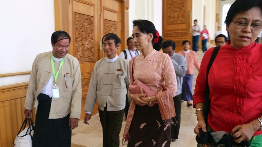 Myanmar opposition leader Aung San Suu Kyi, second right, walks as she attends a regular session of the lower house of parliament Thursday, April 9, 2015 in Naypyitaw, Myanmar. During a press conference later in the day, Suu Kyi says high-level political talks to be held Friday will be meaningful only if they lead to polls set for later this year being free and fair. (AP Photo/Khin Maung Win)