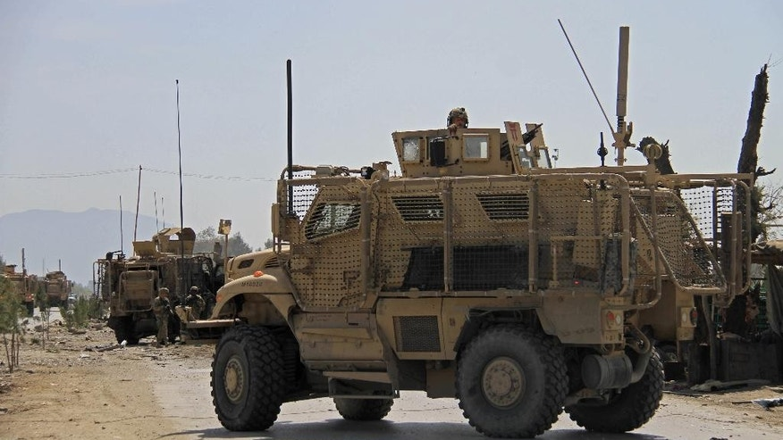 U.S. military vehicles stage at the site of a suicide attack that targeted a convoy of American troops in Jalalabad, east of Kabul, Aghanistan, Friday, April 10, 2015. An Afghan official says the bomb killed and wounded several civilians. The Taliban have claimed responsibility for the attack. (AP Photo)