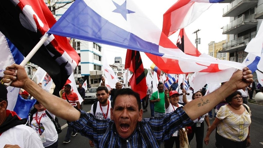 "A demonstrator holds up a Panamanian flag during a protest march by the participants of the ""Cumbre de los Pueblos"" or ""People's Summit,"" against U.S. policies in Latin America, in Panama City, Thursday, April 9, 2015. Panama will host the Summit of the Americas on April 10-11. (AP Photo/Arnulfo Franco)"