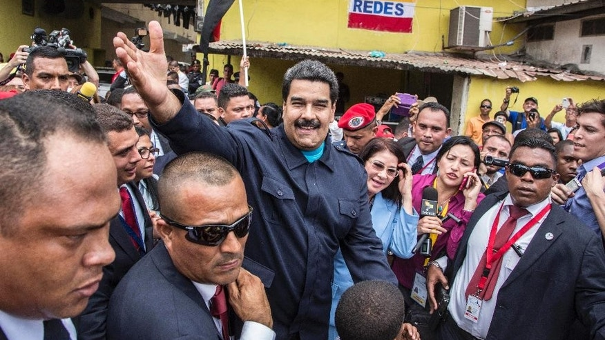 "Venezuela's President Nicolas Maduro greets supporters before a ceremony at a monument in  honor of the victims of the 1989 U.S. invasion, in the Chorrillo neighborhood which saw the heaviest fighting during the invasion, in Panama City, Friday, April 10, 2015. A crowd of several hundred chanted in Spanish, ""Maduro, stick it to the Yankee!"" (AP Photo/Ramon Espinosa)"